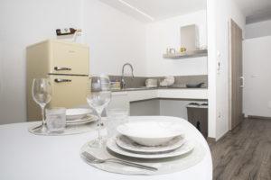 angolo cucina sospesa con dettaglio tavolo apparecchiato e frigo