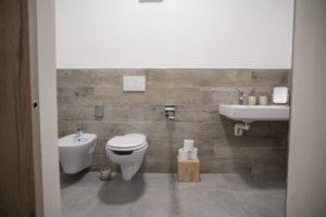 vista frontale del bagno con sanitari sospesi maniglione a destra o sinistra del wc, posta rotoli con base in legno di cedro e lavabo sospeso. da sinistra a destra troviamo bedet, wc e lavabo
