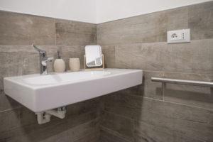 lavabo sospeso in ceramica bianco su parete in gres effetto legno. sulla parete a destra sostegno in acciaio utilizzabile come ausilio da persone con disabilità ma anche come porta asciugamano