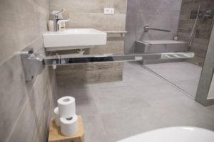 panoramica parziale bagno con maniglione di sostegno aperto del wc, a seguire lavabo e sullo sfondo zona doccia a filo pavimento con seduta e altro maniglione aperto