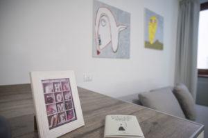 dettaglio di appartamento con quadri astratti, fatti a mano da ragazzi con disabilità