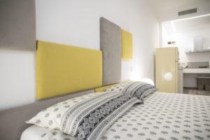 primo piano del letto, guanciali e testiera a rettangoli appesi al muro di varia grandezza e posizione in tessuto giallo e grigio con sullo sfondo la cucina