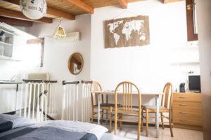 ona living con tavolo e sedie in legno, quadro in legno raffigurante il mondo su parete scorcio di angolo cottura con scala a chiocciola a salire e tv su lato di destra