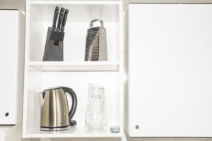 primo piani di utensili presenti in cucina: set coltelli di color nero, grattugia di acciaio, brocca in vetro e bollitore