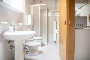 bagno esteso in lungo con tutti i servizi sulla parete sinistra : lavabo, bidet, wc e in fondo box doccia cianco. sull'altro lato termosifone e porta in legno