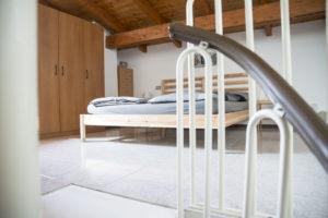 letto in legno di pino con testiera a listarelle con ampio armadio sulla sinistra. vista da ultimo gradino della scala a chiocciola con dettaglio su ringhiera