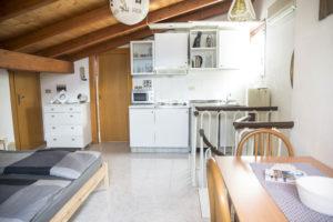 panoramica su zona living e cucina con porta di accesso al bagno nella parete frontale
