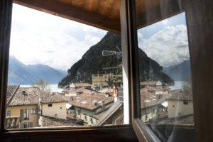 sguardo fuori dalla finiestra con vista sui tetti ed in fonso scorcio del lago in cui si tuffano le montagne