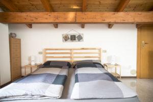 letto in legno di pino con testiera a listarelle . comodini dello stesso legno e abatjour bianche. sulla parete sotto il soffitto in legno piccolo quadretto rettangolare con cuoricino e legnetti