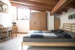 panoramica su zona living sulla sinistra con tavolo da pranzo e letto sulla destra . in fondo su parete ampio armadio e finestra
