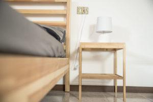 zoom su letto e comodino in legno con abatjour moderna di forma circolare