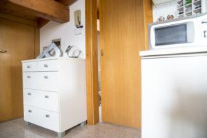 """nel dettaglio 2 mobili accanto alla porta di ingresso al bagno: sopra quello sulla destra troviamo il microonde, sopra quello di sinistra un vaso portacaramelle in vetro e acciaio e una grande lettera """"P"""" in rilievo freestanding"""