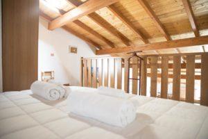 dettaglio parte di letto su soppalco con tetto in legno