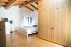 stanza da letto su soppalco con pavimento e tetto in legno, con grande armadio, tv, ventilatore e finestra a pavimento sullo sfondo