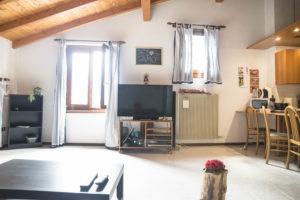 vista da divano della parete frontale con due finestre con al centro smart tv da 50 pollici