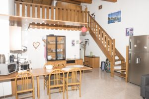panoramica su zona cucina e scala che porta al soppalco e grande frigo ai piedi della scala