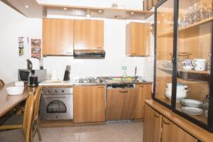 angolo cucina completa di forno e lavastoviglie con dettaglio della credenza a destra e tavolo a penisola a sinistra della stessa