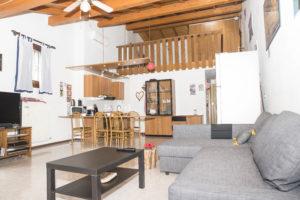 panoramica della zona living angolo cottura e soppalco con camera e alto soffitto con travi a vista mansardato.