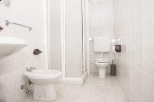 Bagno con lavandino e bidet sul lato sinistro e box doccia e wc sulla parete frontale