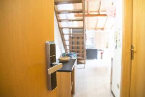 porta ingresso appartamento apersta con particolare su maniglia elettrica con scheda e sullo sfondo l'interno del loft superior