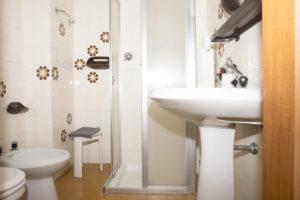 bagno con parete floreale anni 60 . wc e bidet su parete a sinistra , box doccia su parete frontale e su parete a destra lavabo