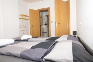 dettaglio letto con sullo sfondo porta ingresso bagno con doccia e porta ingresso camera da letto