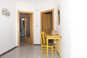 andito con scrittoio giallo con una sedia, sul fondo 2 porte: una verso la zona living una verso la camera da letto con bagno