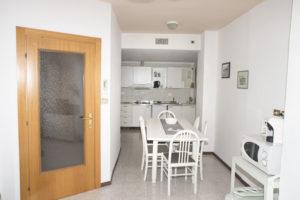 soggiorno zona living con tavolo lungo rettangolare bianco grande per 6 persone e sullo sfondo piano cottura