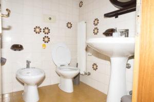 bagno con parete floreale anni 60 . bidet sulla parete frontale posizionato a destra, wc accanto a sinistra e lavabo su parete di destra