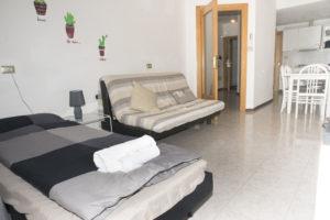 salotto con poltrona letto aperta, divano e tavolo con vista su cucina
