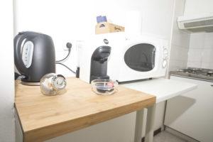 primo piano del bollitore, macchina del caffe e microonde nella zona cucina