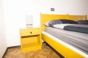 letto pronto con piumino a quadri e comodino abbinato di color giallo con abatjour moderna di forma rettangolare
