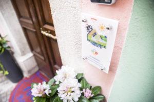 zoom su targa residence e fiori accanto al portone d'ingresso
