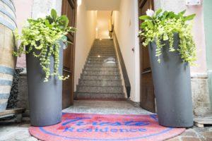 zoom su vasi di fiori accanto al portone d'ingresso aperto e tappeto residence trieste con vista sulle scale