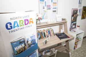 espositore con brochure del territorio e libri riposti su desk con sopra una bacheca informazioni varie
