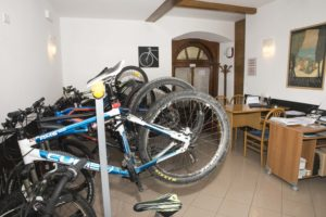 varie mtb e bici appese nella bike room video sorvegliata e sullo sfondo la zona reception